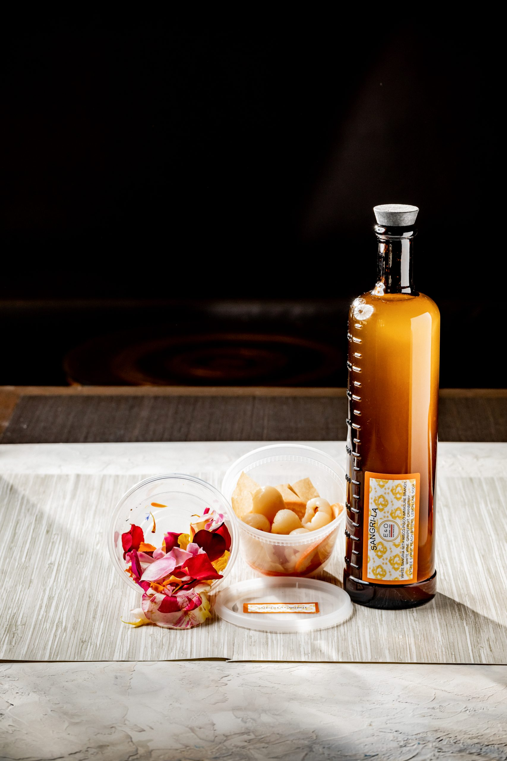 a beverage in an amber colored glass with two containers of drink garnishes to-go.