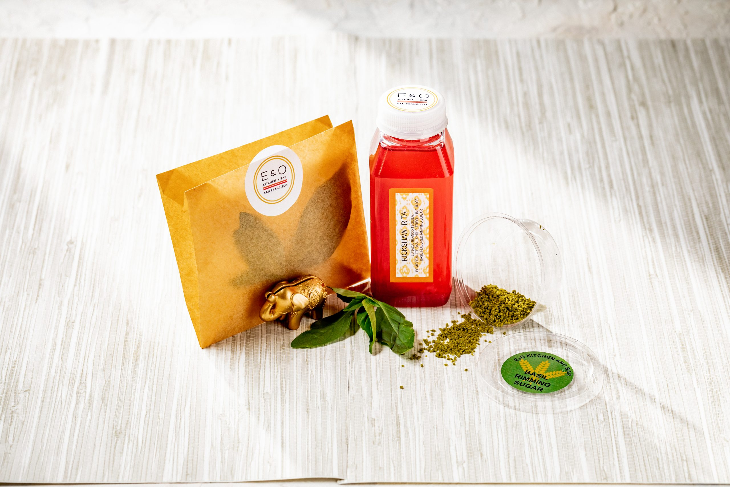 a to-go drink in a bottle with basil riming suge in a smal container and mint leaves for garnish in an envelope