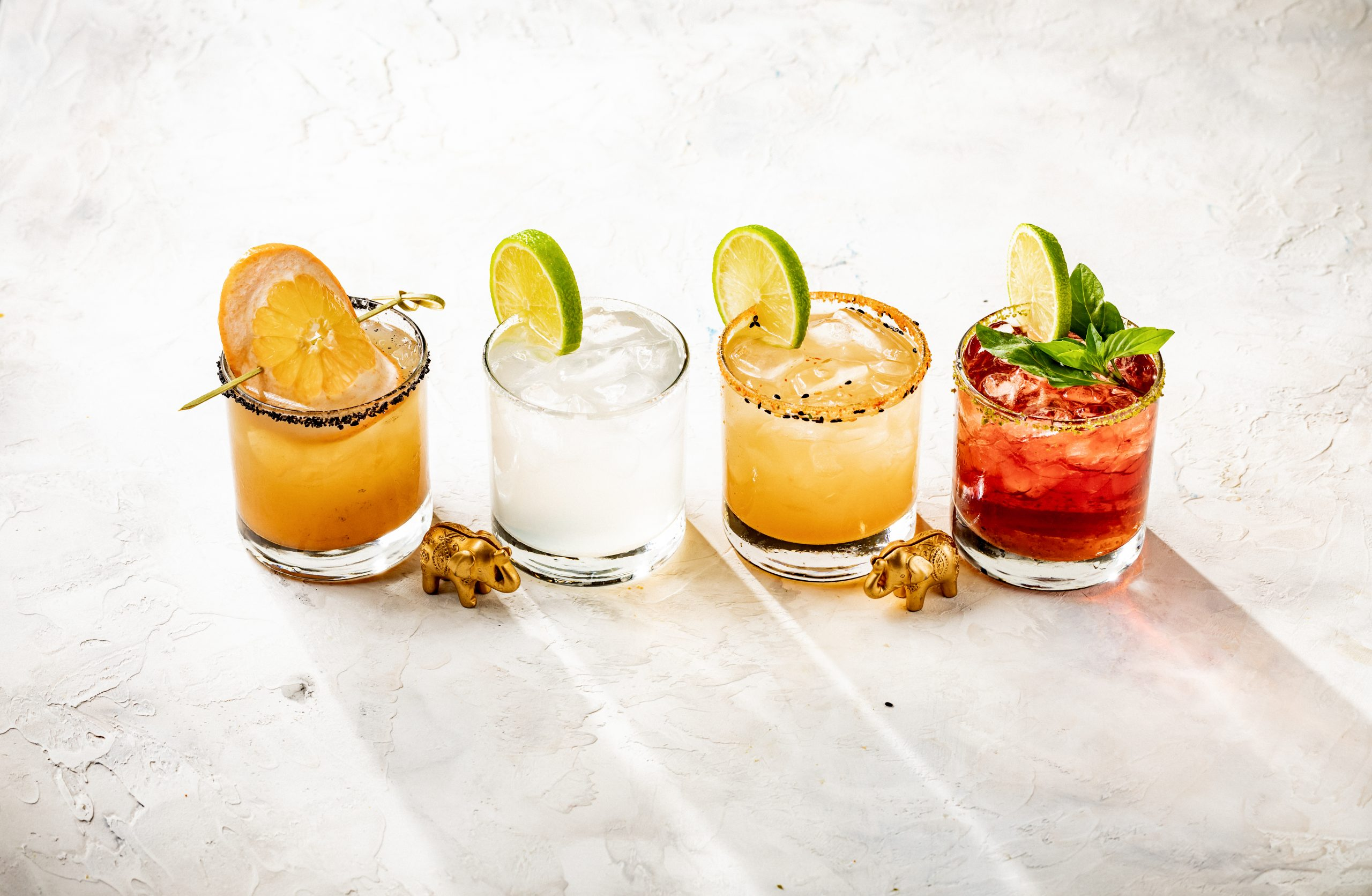 four different colored drinks in glasses with orange and lime wedge garnishes. two elephant trinkets on the table with the glasses.