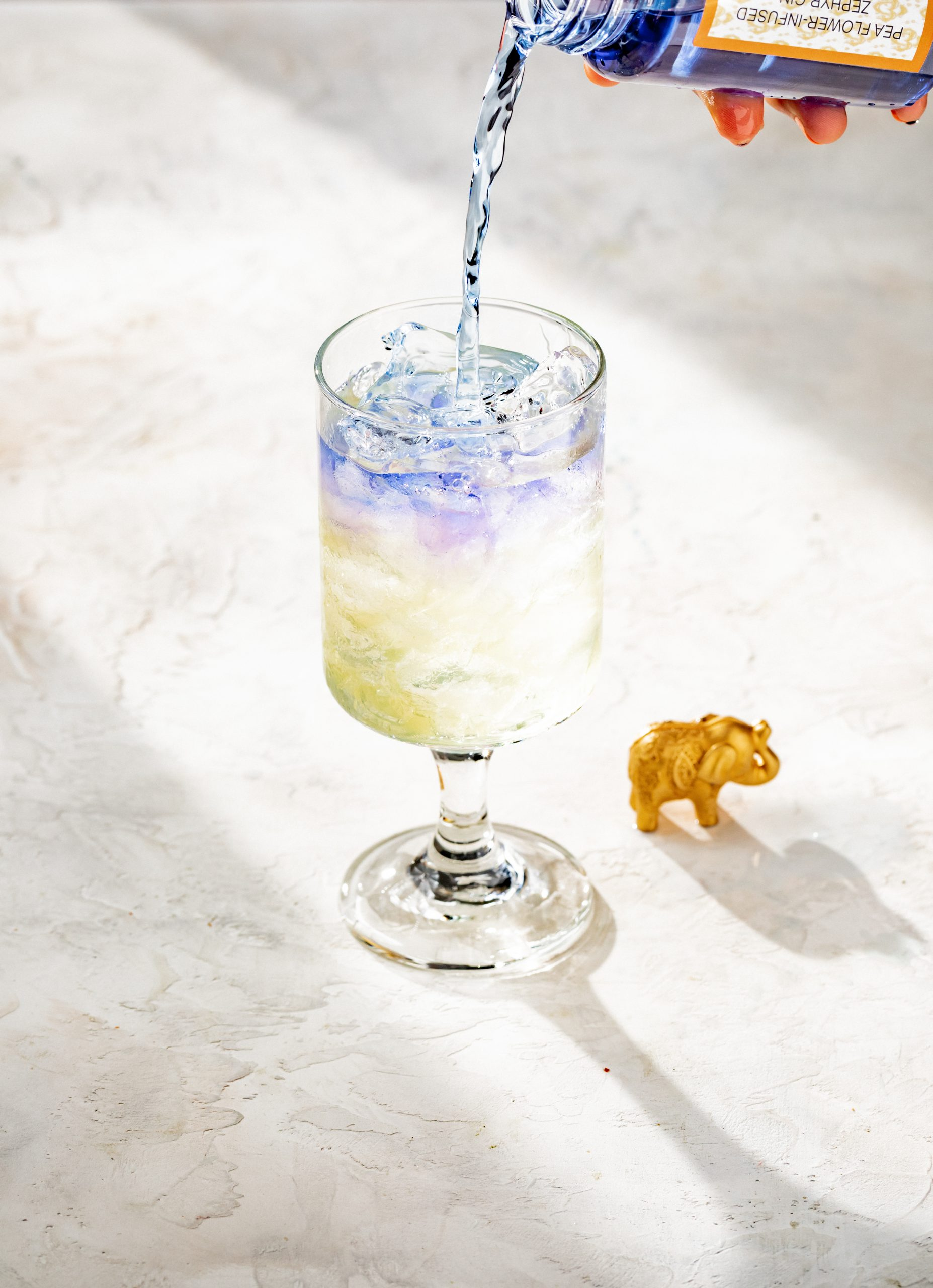 A blue colored beverage being poured into a glass with ice and a small elephant trinket on the table beside the glass