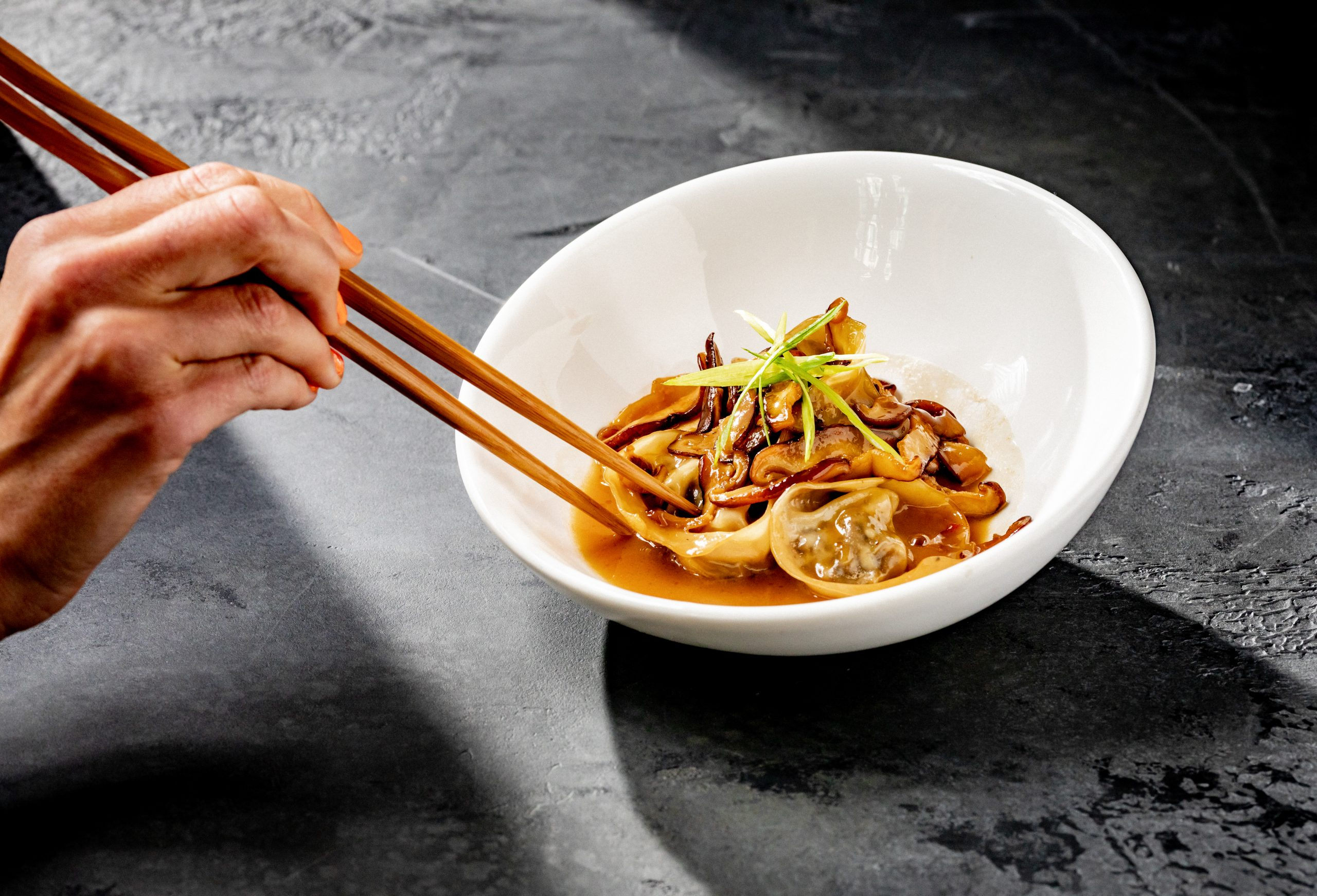 dumplings and garnish in a bowl with someone using chopsticks to hold a dumpling