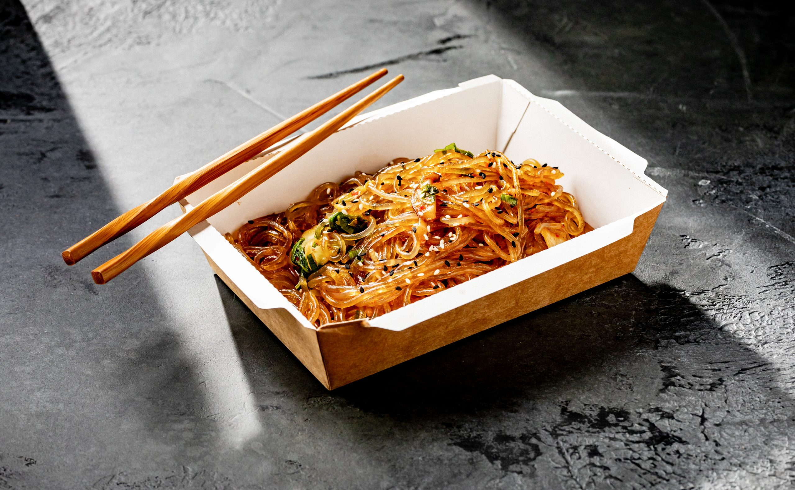 a to-go meal from E&O Kitchen with chopsticks