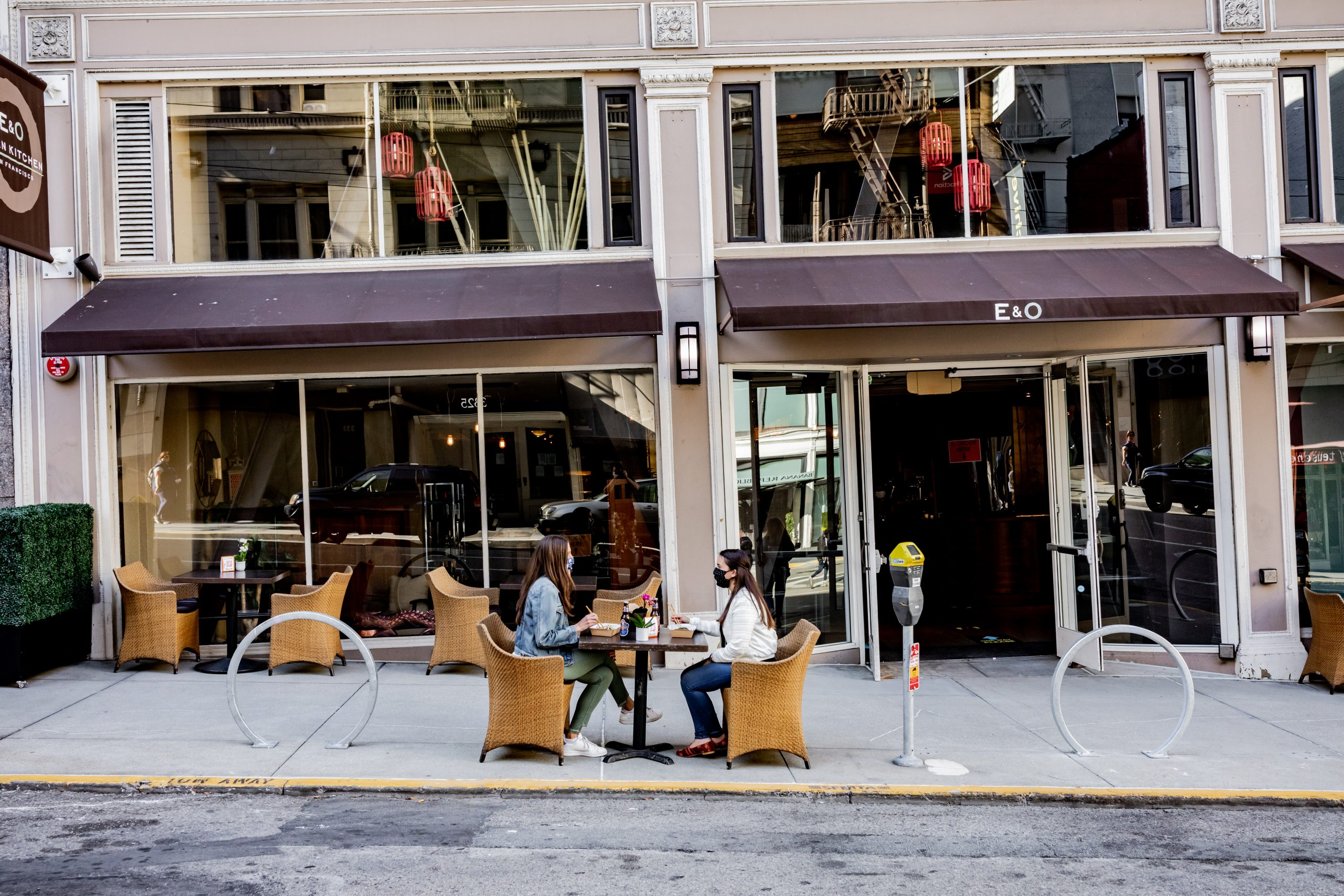 two guests sitting outside at a table in front of E&O Kitchen