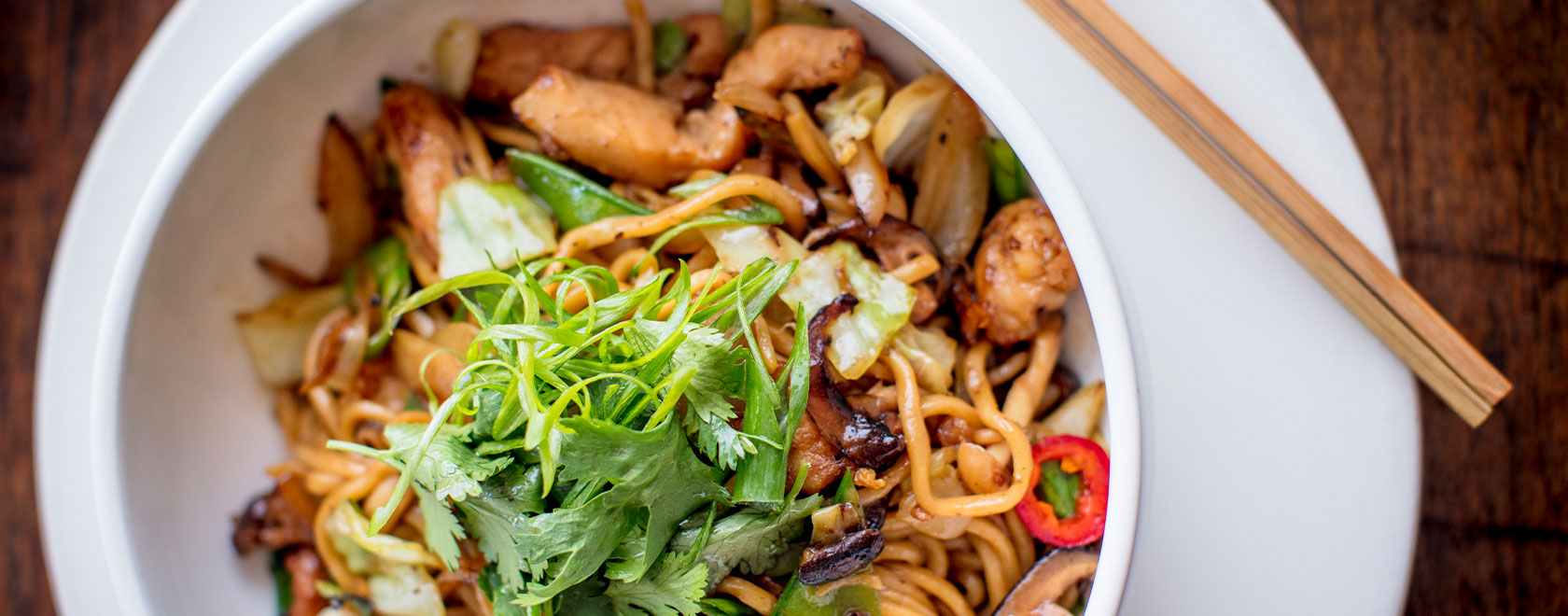 lo mein dish with meat and vegetable garnish on top, chopsticks are beside the bowl