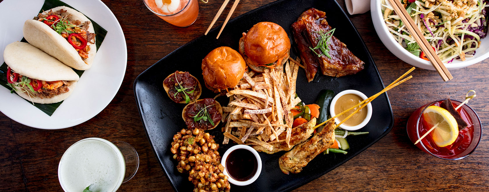an aerial view of a spread of entrees from E & O Kitchen and drinks set out on a table